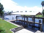 View of the back yard, dock, and covered boat lift. Fishing rods are available in the house.
