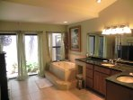 The master bathroom offers a garden tub, walk-in shower and screened private garden area