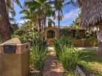 Lush plantings and dozens of palm trees invite you right up to this tropical Spanish-style abode.