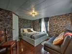 The spacious first bedroom features a queen-sized bed and a plush leather sofa.
