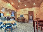 The expansive living area features an antique piano, 2-person breakfast table, 4-person round table, and 10-person...