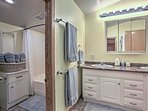 This bathroom features a double sink, shower/tub combo, and plenty of towels.