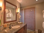This full bathroom features copper slate tiles and plenty of counter space.