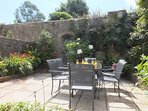 The beautiful tranquil enclosed suntrap of a walled garden with patio furniture for 6 people