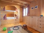 Bunk room with four adult size bunk bed, each with shelf, lamp, privacy curtains. Second TV for kids