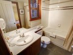 The full sized bathroom comes complete with vanity and shower-tub combination.
