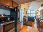 The well stocked kitchen is complemented with newer stainless steel appliances.