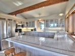 Stainless steel kitchen appliances with tile counter-tops in a sunlit kitchen.