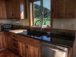 Granite counter-tops, stainless steel appliances, and forest views.