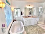 The attached master bathroom has double sinks,  and a claw foot tub, shower.