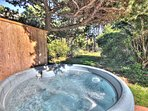 The hot tub tucked away among the trees next to the house for your relaxation.