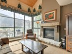 The large living area features vaulted ceilings and large windows framing mountain views.