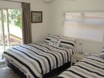 Side bedroom - Queen and King Single. Ceiling fan. Verandah access