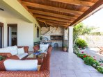 Fully equipped charcoal barbecue with a wood oven & dining table under a pergola