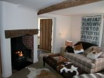 The main sitting room has an open fireplace with woodburning stove