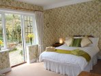 The master bedroom has French windows leading out to the upper garden
