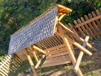 Hand crafted bench swing with a pine shingled roof