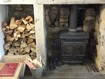 Logs (supplied from November - March) are stacked in the inglenook fireplace.