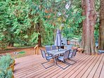 Giant cedar trees, deep forest views, and roaming deer can be seen from the deck.