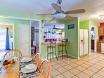 The fully equipped kitchen flows seamlessly into the dining area which hosts a  2-person breakfast bar and 6-person...