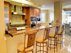Breakfast bar at granite countertops offers extra seating