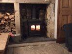Wood burning stove set in the inglenook fireplace