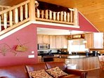 Rustic banister leads to upper level loft with four twin beds.