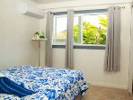 Bedroom 2 with queen bed. Look at the beautiful tropical plants in the window!
