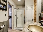 The main bath holds a large stall shower, repurposed marble topped vanity with a copper sink!