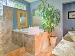 Rinse off in the spa-like bathroom that offers a bath, walk-in shower, and dual sinks.