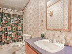 Wash up in the master en-suite, equipped with a single vanity and shower/tub combo.