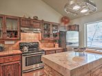 Beautiful wood cabinetry, tile countertops, a stunning center island, and stainless steel appliances make the fully...