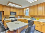 The kitchen is fully equipped with modern appliances, cookware, and dishware.