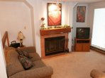 Relax and unwind in the spacious living area, complete with fireplace and flatscreen TV. Photos are representative.