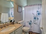 The third bathroom has a single sink, large vanity mirror, and a tub/shower combo.