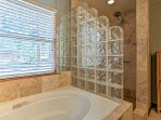 Wash up in the master en-suite, equipped with a lavish walk-in shower, Jacuzzi tub, and single vanity.