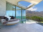 Main bedroom patio has glass floor and handing daybed perfect for lazing in