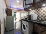 Kitchenette with cutlery, crockery, washing machine, induction plate, toaster, microwave, kettle