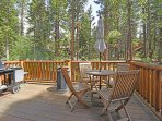 Back deck accessible through the kitchen, includes furniture and a grill to take in the forest setting