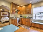 The kitchen features stainless steel appliances and pristine granite counter space.