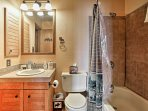 The en-suite master bathroom of the loft hosts a shower/tub combo and vanity sink.