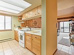 The kitchen is fully equipped with modern appliances, a double sink, and ample counter space.