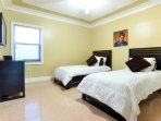 Fifth bedroom with single beds and a large LCD TV