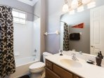 The fourth bathroom has a tub/shower combination with a large vanity and mirror
