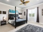 The master bedroom is large and has a king sized four poster bed