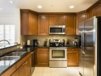 Beautiful granite counter tops line the kitchen and surround the stainless steel appliances