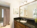 The second master bathroom has a large mirror and granite counter tops