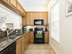 The fully equipped kitchen opens into the living room with ample room on the granite counter tops to prepare a lavish...