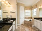 The master bathroom has a large tub, walk in shower and dual vanities