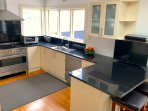 Fully equipped modern kitchen with fridge, microwave, gas/electric stove, dishwasher and  TV